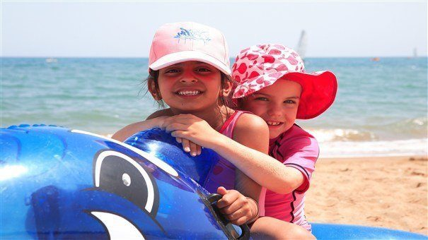 Two young girls on whale inflatable.