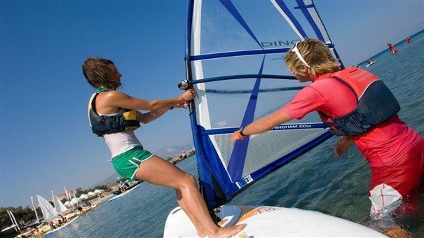 instructor teaching guest how to windsurf in lakitira
